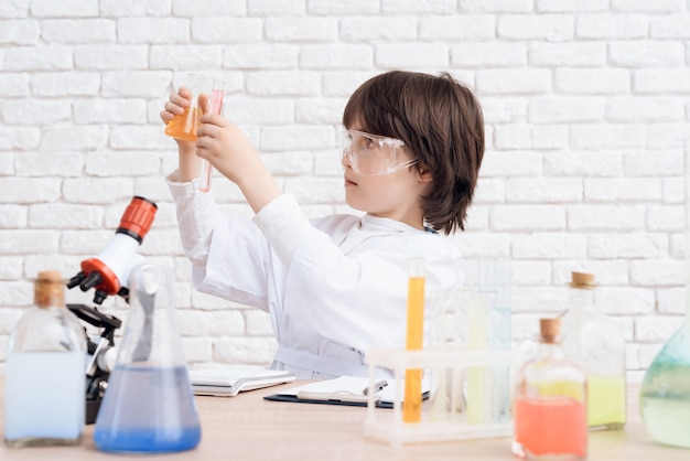 Man looks at the chemical reactions in the flask Premium Photo