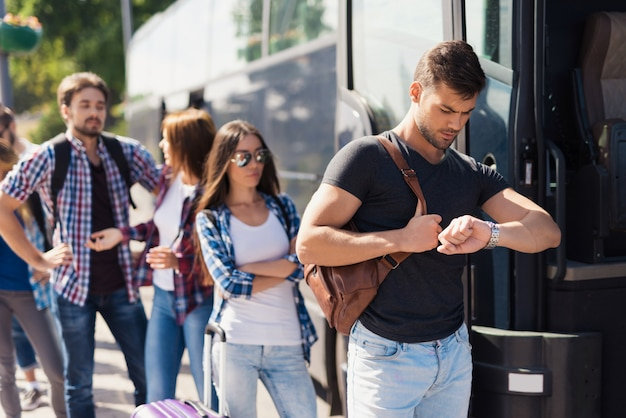 Man looks at his watch and gets on the bus. Premium Photo
