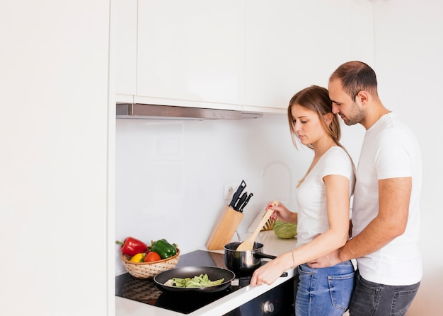 Man loving his wife coking food on new electric stove with induction cooktop in kitchen Free Photo