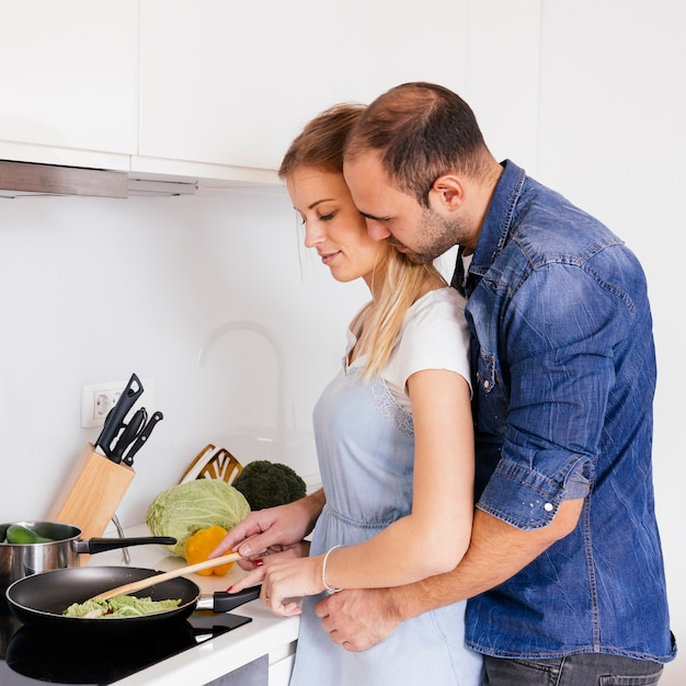 Man loving his wife cooking food on induction cooktop in kitchen Free Photo