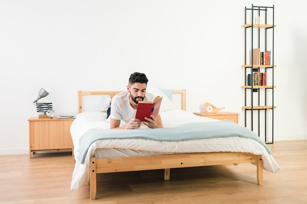 Man lying on bed reading the book in the bedroom Free Photo