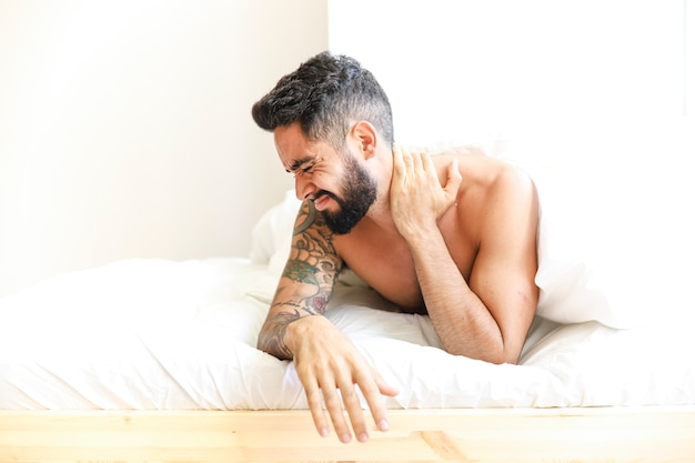 Man lying on bed suffering from neck pain Free Photo