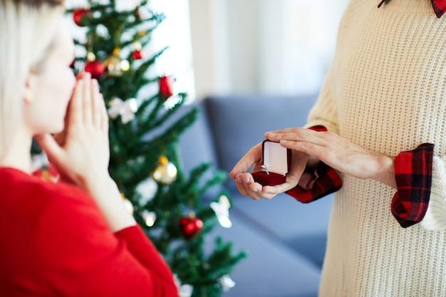 男はクリスマスの日に彼のガールフレンドにプロポーズをします 無料写真