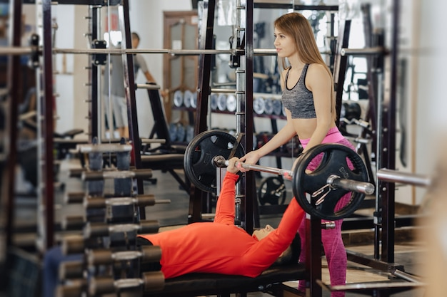 Man makes a bench press, he is insured by a girl coach, a sports gym theme Premium Photo