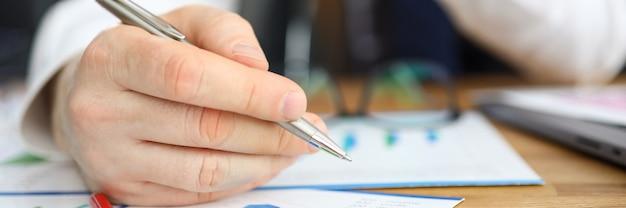 男は財務報告に寄りかかる編集を行います Premium写真