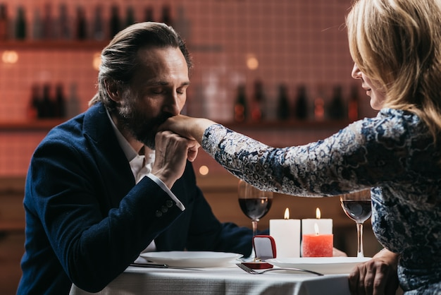 Man makes a marriage proposal and kisses the hand of a woman in a restaurant Premium Photo