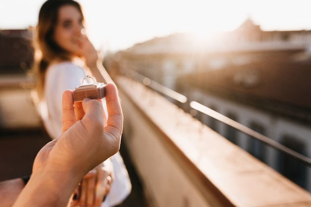 Мужчина делает предложение руки и сердца девушке, стоящей на крыше в солнечный день Бесплатные Фотографии