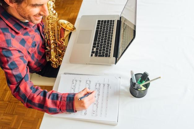 Человек делает заметки на нотах во время прохождения онлайн-курса саксофона Premium Фотографии