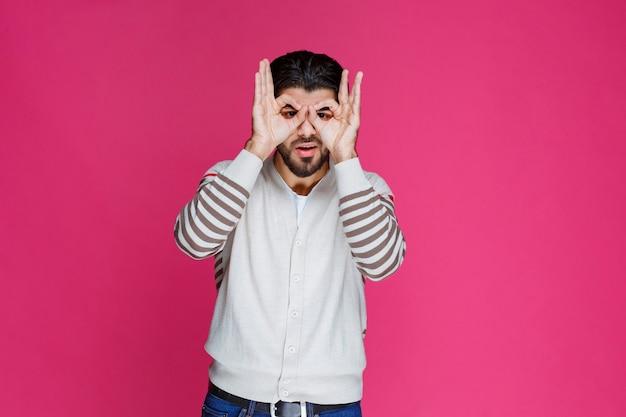 손가락으로 올빼미 얼굴과 눈을 만드는 남자. 무료 사진