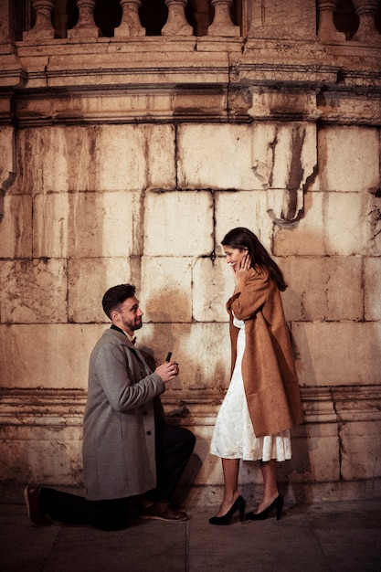 Man making proposal to young woman in street Free Photo