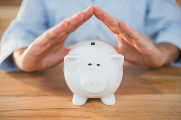 Man making a roof gesture on piggy bank Free Photo