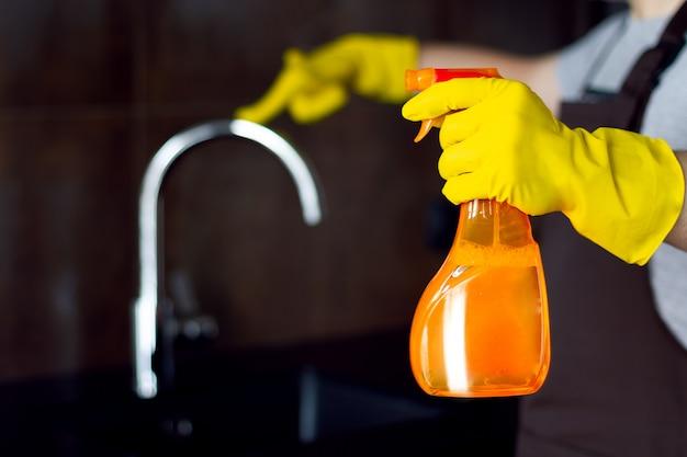 黒いテーブルとキッチンタップを輝くモダンなロフトの金属クロムを洗浄するクリーナーのオレンジ色のボトルと黄色のゴム手袋のクリーニングサービスから男性男性クリーナー手。男は台所を掃除します。 Premium写真