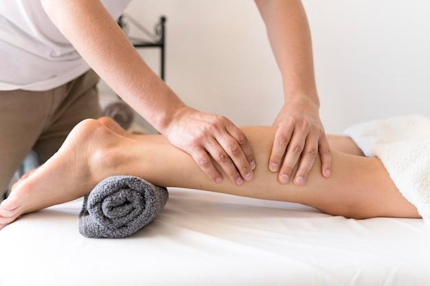 Uomo che massaggia le gambe del cliente Foto Gratuite