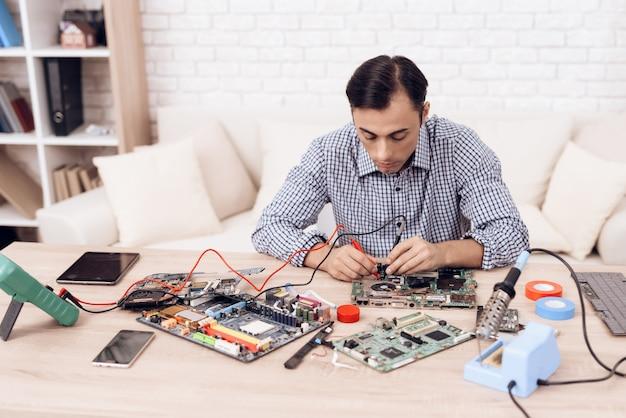 Man master repairing appliances on table at home. Premium Photo