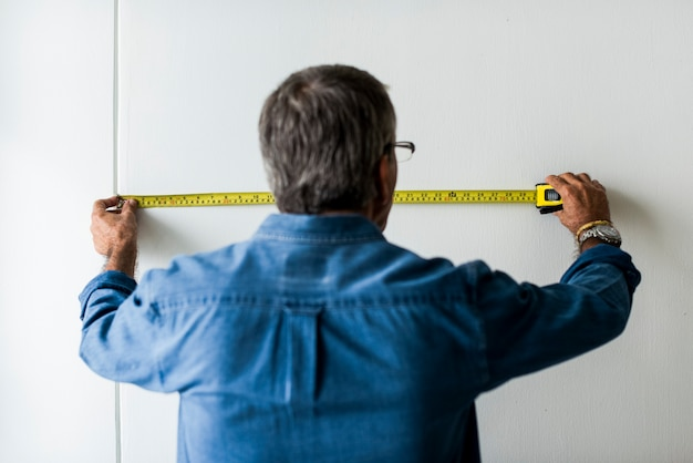 Man measuring the wall with a measuring tape Free Photo