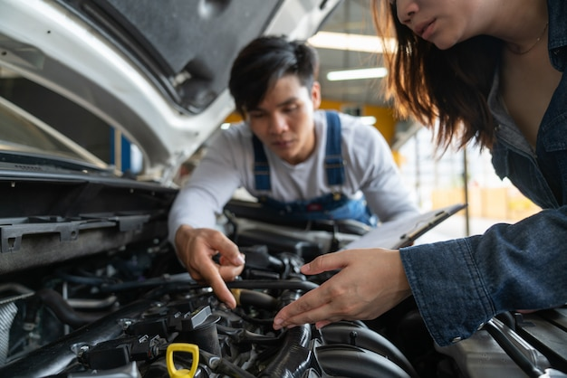 Man mechanic and woman customer look at the car hood and discuss repairs. Premium Photo