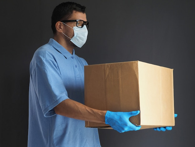 Man in medical mask and gloves delivered the parcel. courier with a cardboard box. parcel delivery service during epidemic pandemic coronavirus 2019-ncov, covid-19 virus. Premium Photo