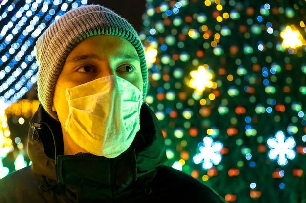 Un uomo in maschera medica e una giacca invernale di notte, decorazione di natale sullo sfondo a chisinau, in moldavia Foto Gratuite