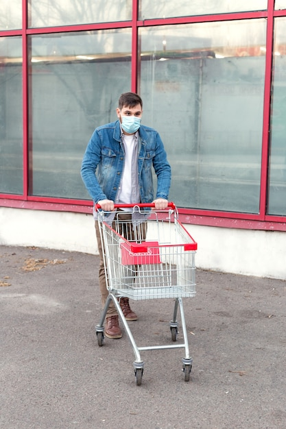 Man in medical protective mask with empty supermarket trolley. Premium Photo