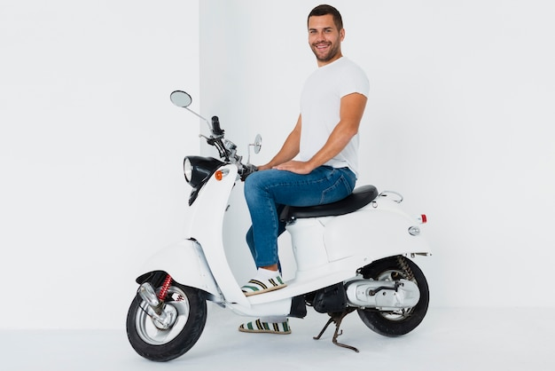 Man on motor scooter being happy and looking at camera Free Photo