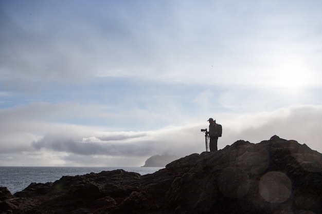 Man on a mountain with a tripod and a camera. sport and active life Premium Photo