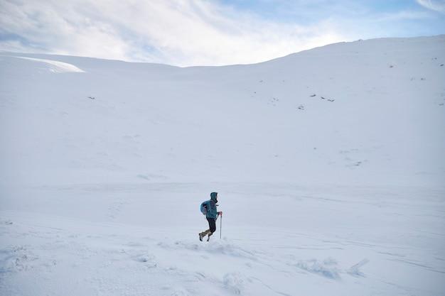 언덕에 걷는 남자 산악인은 신선한 눈으로 덮여 있습니다. 카르 파티 아 산맥 프리미엄 사진