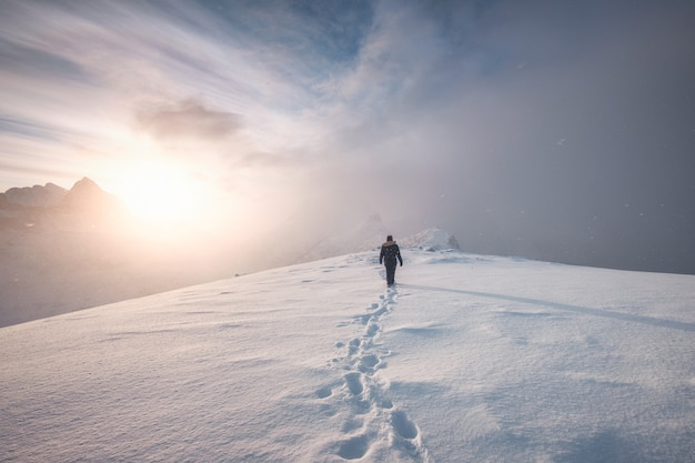Man mountaineer walking with snow footprint on peak ridge Premium Photo