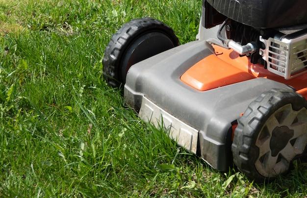 Человек движется с газонокосилкой, косит зеленую траву Premium Фотографии