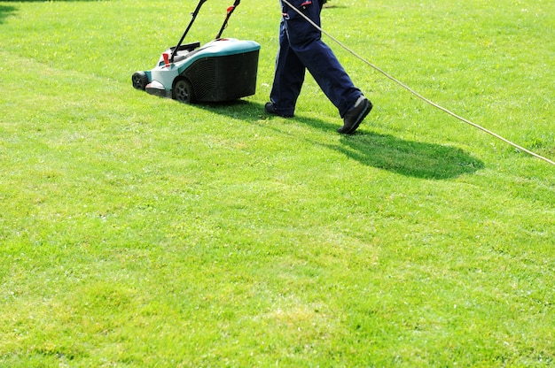 Man moves with lawnmower & mows green grass Premium Photo