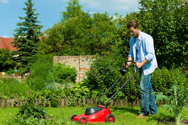 Man mowing the lawn with machine Premium Photo