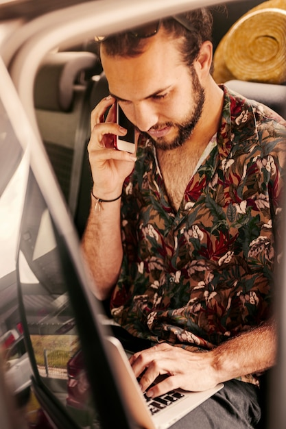 Man negotiating and working on laptop in car Free Photo