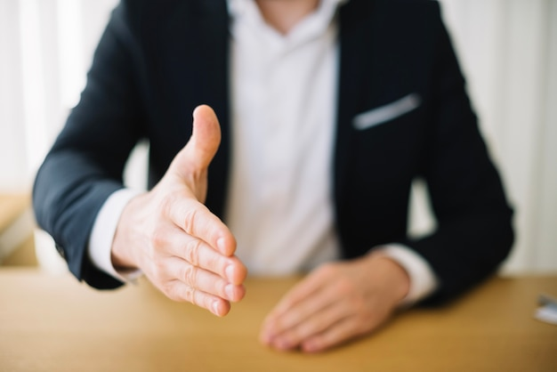 Man offering hand in office Premium Photo