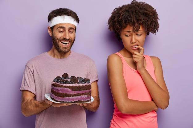 男は妻に美味しいケーキを提供します。困惑したアフリカ系アメリカ人の女性は夫に戻り、甘いデザートを誘惑して見つめ、スポーツウェアを着て健康を保つためのジャンクフードを避けます。痩身、カロリー 無料写真