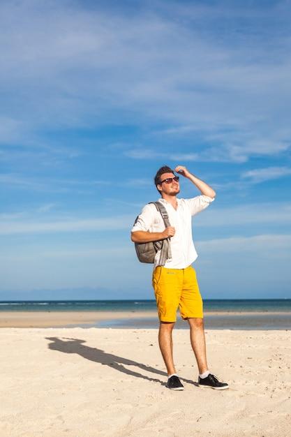 笑顔で流行に敏感な明るい服を着ているビーチの男 無料写真