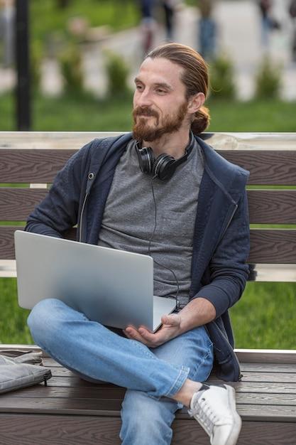 Человек на скамейке на открытом воздухе с ноутбуком Бесплатные Фотографии