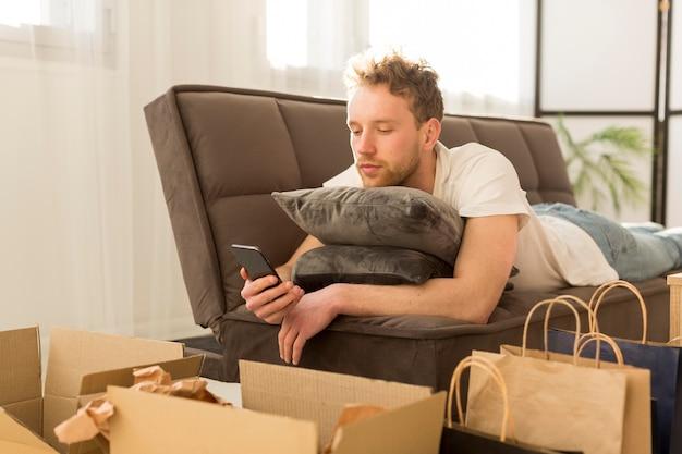 Мужчина на диване держит смартфон Бесплатные Фотографии