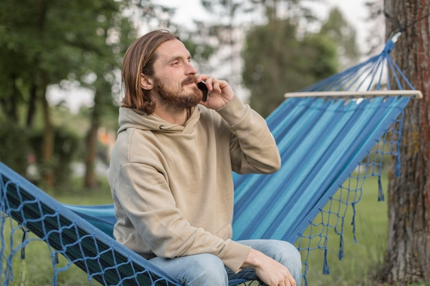 Человек в гамаке на природе, говорить на смартфоне Бесплатные Фотографии