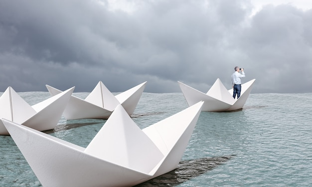 Человек на бумажной лодке с биноклем плывет по морю. Premium Фотографии