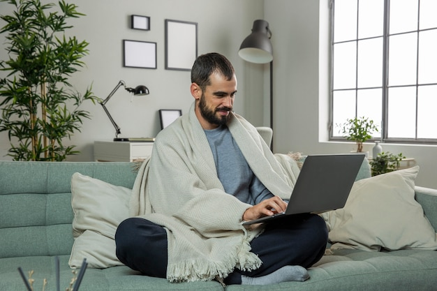노트북에서 일하는 소파에 남자 무료 사진