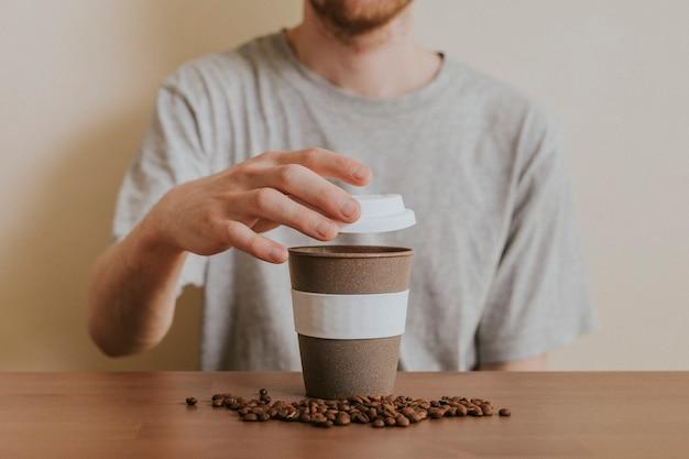 再利用可能なコーヒーカップを開く男 無料写真