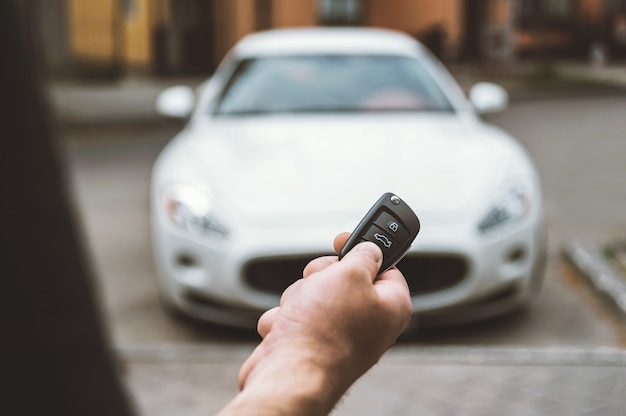 The man opens the car with a keychain, in the background is a white car. Premium Photo