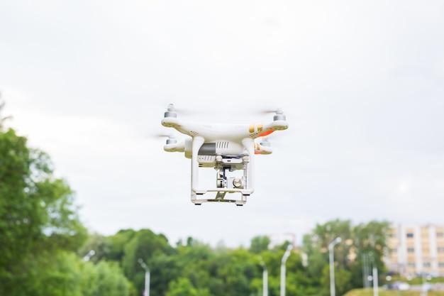 Человек, управляющий дроном, летит или зависает с помощью пульта дистанционного управления на природе Premium Фотографии