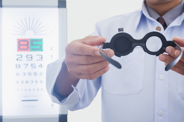 Man at optician holding eyes examined tool to put on patient Premium Photo