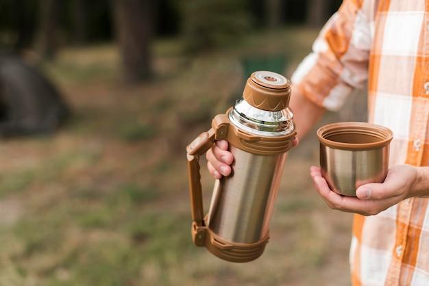 Человек на открытом воздухе, кемпинг и горячий напиток Premium Фотографии