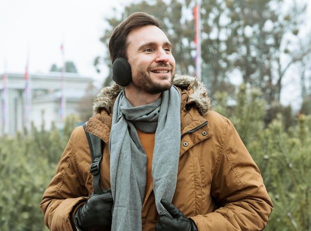 Uomo all'aperto in inverno che indossa cuffie antirumore Foto Gratuite