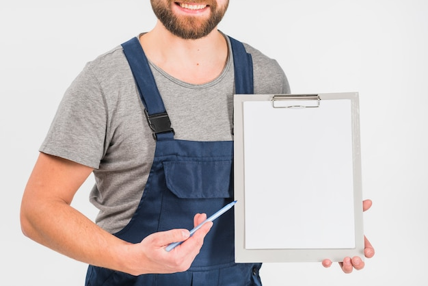 Man in overall showing clipboard with blank paper Free Photo