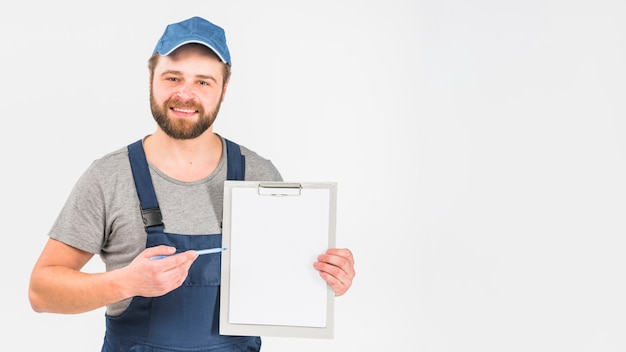 Man in overall showing clipboard with paper Free Photo