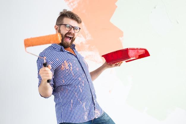 Человек рисует внутреннюю стену нового дома Premium Фотографии