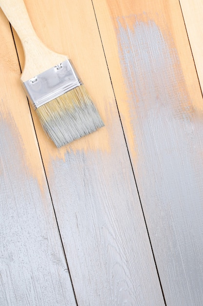 A man paints wooden boards in gray paint brush. Premium Photo
