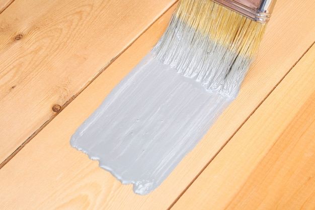 A man paints wooden boards in gray paint brush Premium Photo
